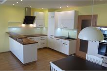 Bílá kuchyň v lesku - pohled od stolu