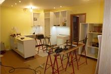 Bílá kuchyň v lesku - pracovní deska kolem dřezu