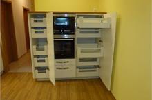 Bílá kuchyň v lesku - skříňka s troubou a mikrovlnkou